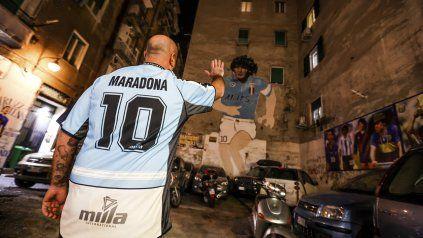 Un hincha del Napoli se acerca a la imagen de Diego Maradona ubicada en el centro de la ciudad.