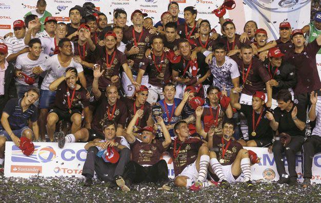 La consagración. El plantel granate levanta la Copa Sudamericana ante su gente. El equipo del Mellizo ganó el certamen con autoridad y quiere la yapa de coronarse en el torneo Inicial.