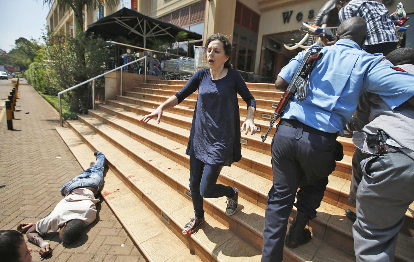 Una de las víctimas fatales yace en el frente del mall mientras una mujer huye despavorida.