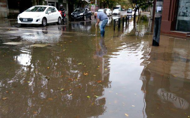 Tapada. Un hombre destapa la boca de tormenta en San Luis y Francia.