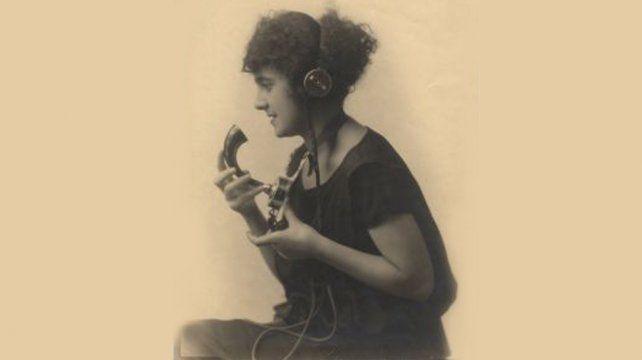 Una mujer habla con una antiguo aparato telefónico a fines del siglo XIX.