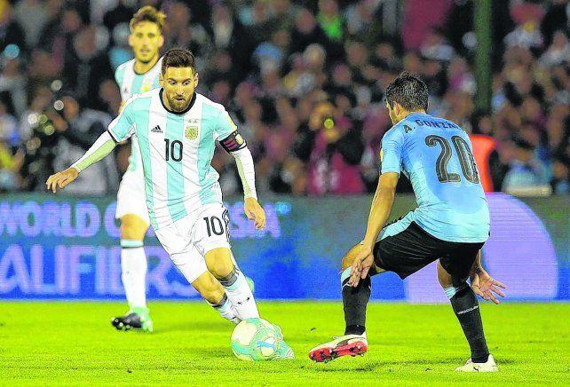Con ojos bien abiertos. Messi tiene la vista fija en la pelota mientras que Alvaro González empieza a resignarse.