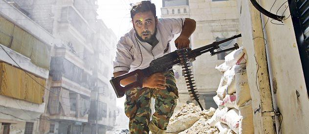 Bajo ataque. Un insurgente corre a protegerse entre las ruinas de la sitiada ciudad de Aleppo.