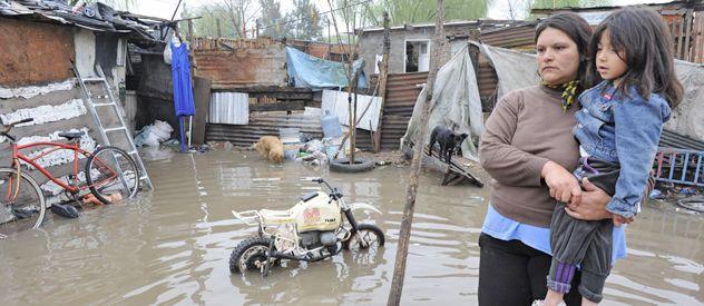 Liliana Montenegro alza a su pequeña hija de 4 años a metros de la vivienda en la que viven en la zona de Nuevo Alberdi. El agua se adueño de todo y ayer esperaban ayuda resignados.