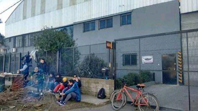 Los obreros que fueron despedidos hacen guardia en la puerta de la fábrica