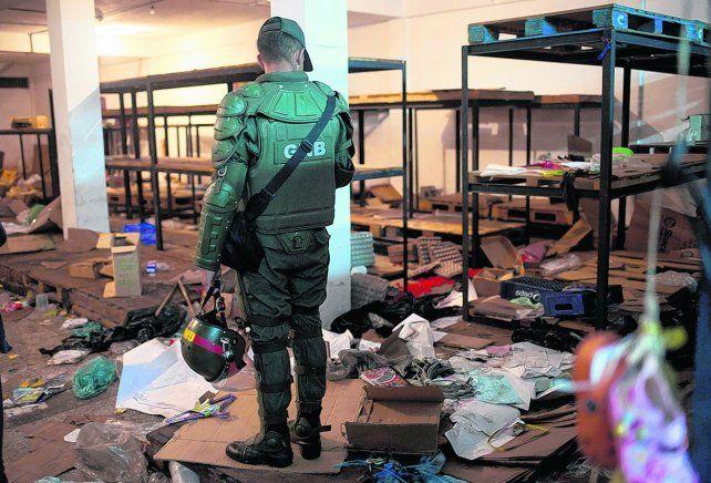 Caos y saqueos. Un miembro de la Guardia Nacional observa cómo quedó un comercio vandalizado por la falta de billetes en Ciudad Bolívar.