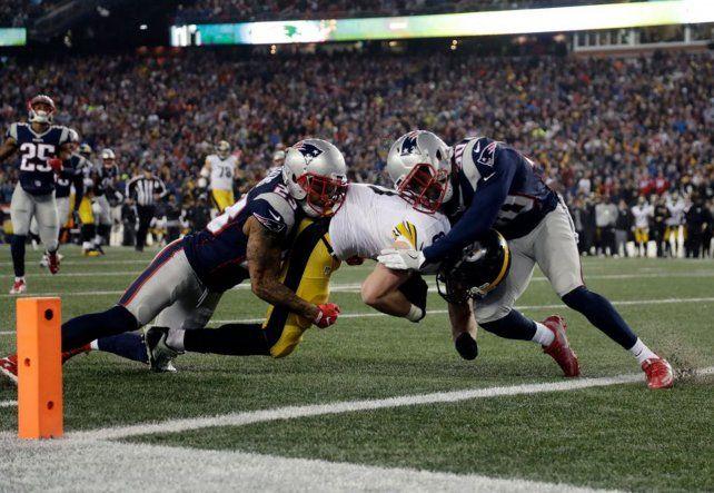 Fricción. Jugadores de New England Patriots tratan de impedir el avance de un rival.