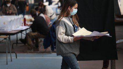 Una votante, cargada con las voluminosas boletas, se dirige al cuarto oscuro en Santiago.