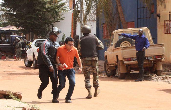 Un par de soldados logra sacar del hotel a uno de los rehenes. (Foto: AP)