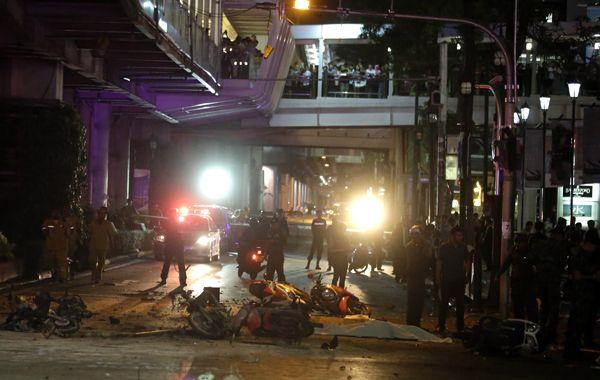 Vecinos y curiosos observan la cruenta escena desde las pasarelas del tren elevado.