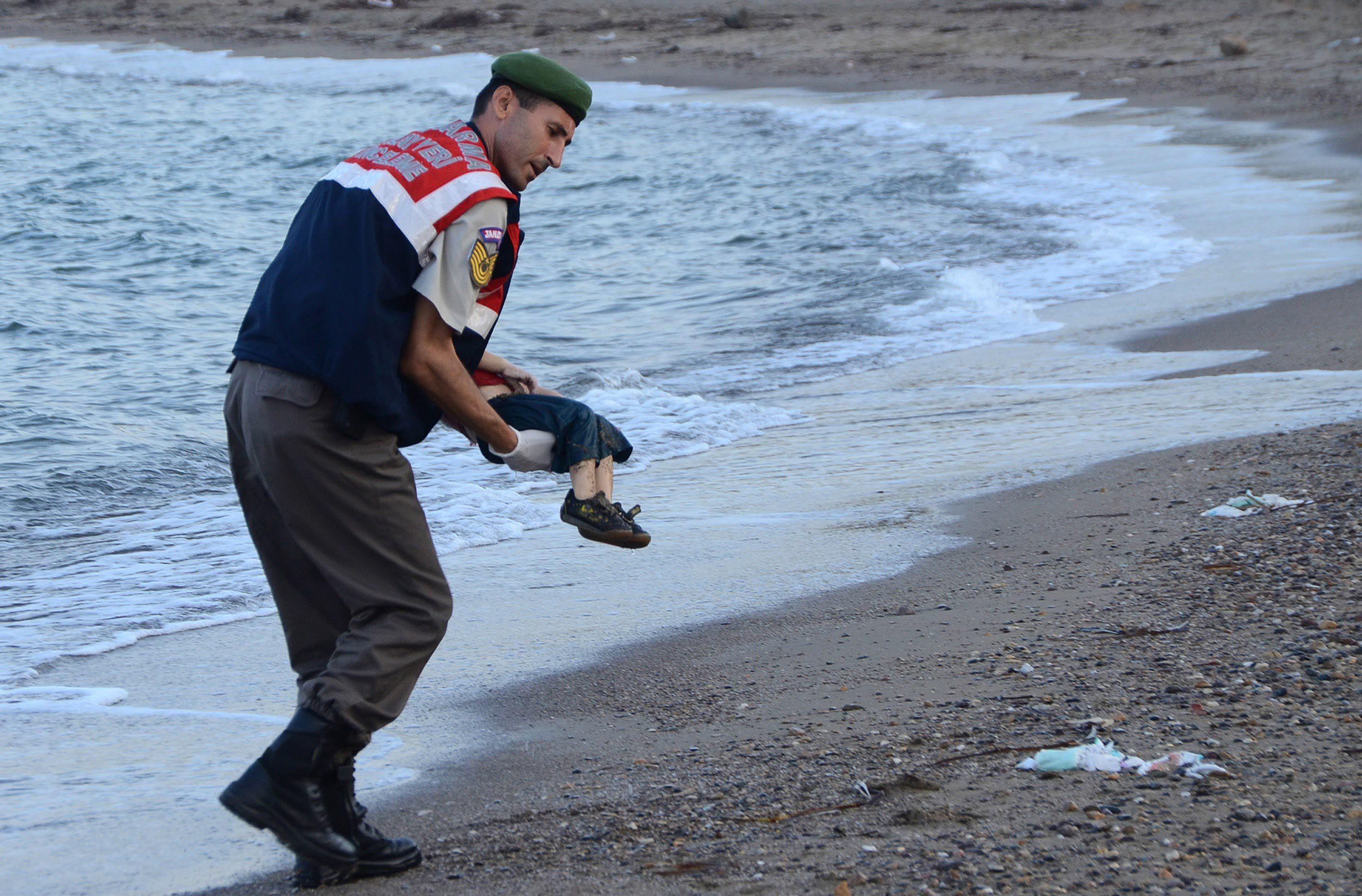 Dramático. Un policía turco recoge el cuerpo sin vida del nene sirio. Otras once personas murieron ahogadas.