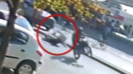 El motociclista ya atropelló a la mujer, que yace en el piso, mientras el conductor sigue haciendo willy. (Captura de video)