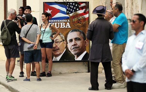 La llegada. Turistas conversan frente a un afiche de Obama y Raúl Castro