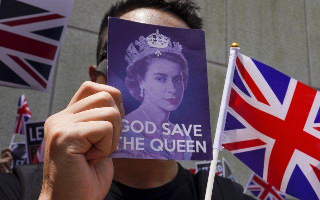 Un manifestante tapa su rostro mientras participa en una manifestación frente al consulado británico en Hong Kong. El gobierno británico está estableciendo un fondo de 43 millones de libras para ayudar a los migrantes de Hong Kong a establecerse en el país.