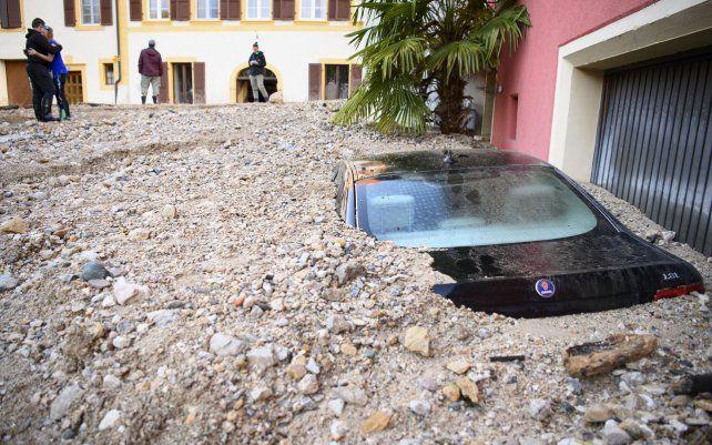 Un hombre consuela a su mujer al observar un automóvil enterrado bajo los escombros después de una violenta tormenta en Cressier