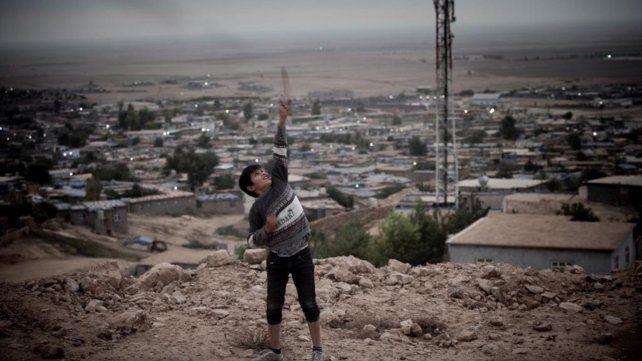 Un niño arroja una piedra al cielo en el campo de refugiados de Makhmur