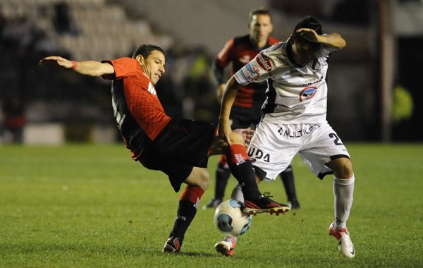 Maxi Rodríguez busca el balón ante Jonathan Ferrari. (Foto: Sebastián Suárez Meccia).