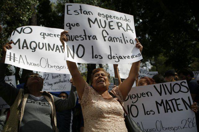 Brazos en alto. Familiares de personas atrapadas en un edificio del barrio Roma Norte protestan ayer.