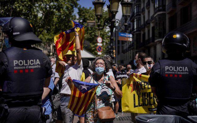 Manifestantes sostienen esteladas o banderas independentistas catalanas durante una protesta contra el primer ministro de España