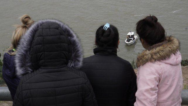 Familiares de Nicolás Verón en el lugar donde el joven cayó al río mientras pescaba.
