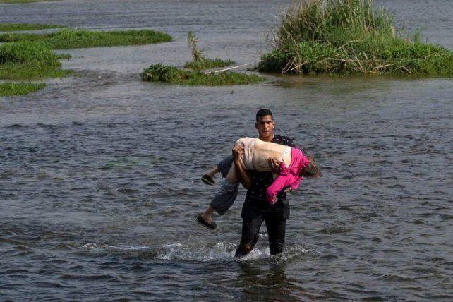Drama en el río Bravo, que separa a México de Texas. Un joven venezolano lleva en brazos, inconsciente, a una anciana. Los dos escaparon de Venezuela.