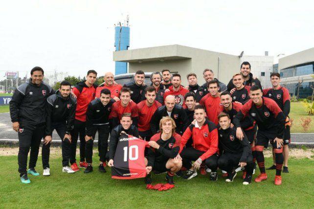 Todos junto a Lio. Messi aceptó gustoso posar con jugadores y colaboradores de Newells