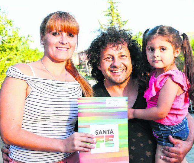 Felicidad. Una familia muestra contenta la escritura de su vivienda.