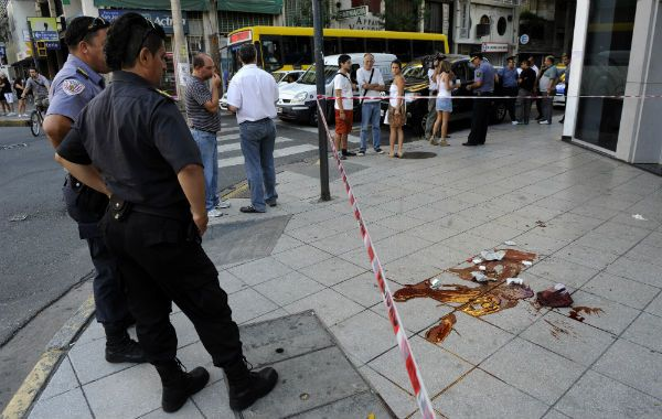 Lo que quedó. Dos policías observan azorados la sangre y los restos de masa encefálica en la vereda donde mataron de un balazo a Maximiliano Rodríguez.