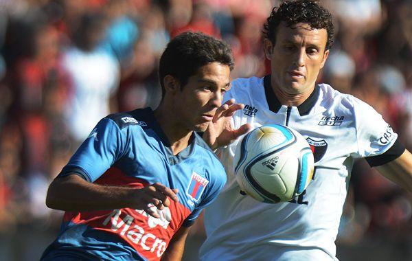 Larrondo intenta un avance para Tigre perseguido por Pablo Ledesma. (Foto: Télam).