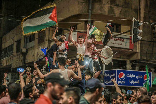 """Partidarios de Hamás celebran la presunta """"victoria"""" sobre Israel en las calles de Gaza."""