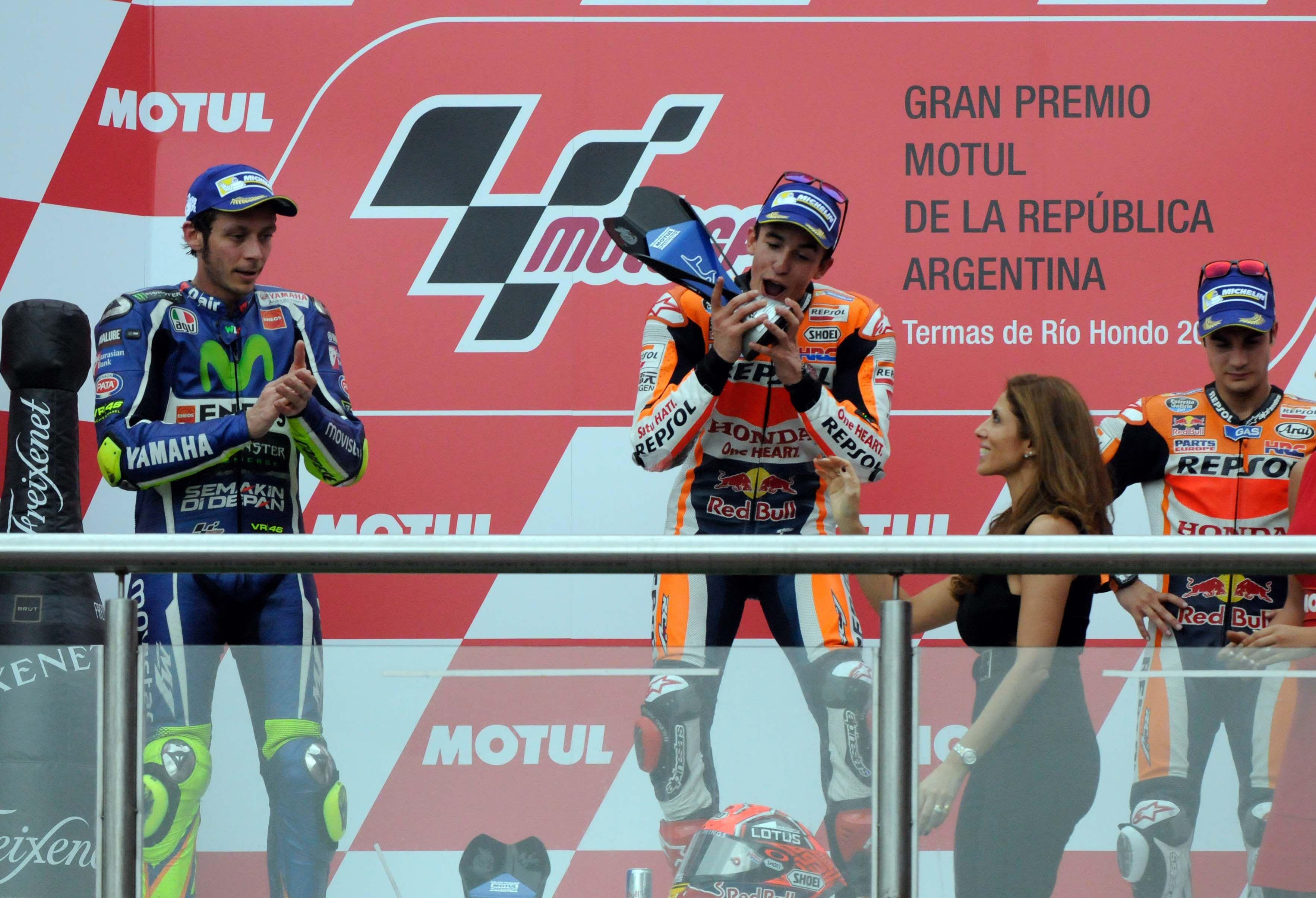 Me lo como todo. Márquez recibe el trofeo y parece querer darle un mordiscón mientras el gran Valentino Rossi aplaude tibiamente.