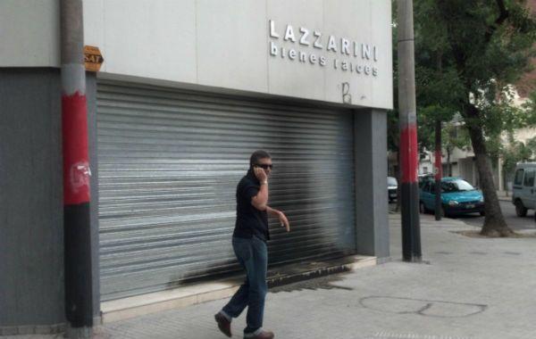 El efecto. Gonzalo Lazzarini frente a la persiana metálica chamuscada de la inmobiliaria atacada a la madrugada.