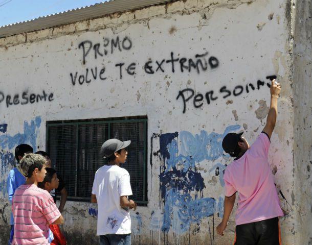 Un grupo de chicos pinta mensajes en recuerdo de un joven. (Foto: S. Salinas)