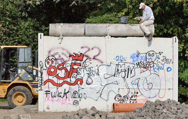 Un obrero repara un trozo del otrora Muro del Berlín.