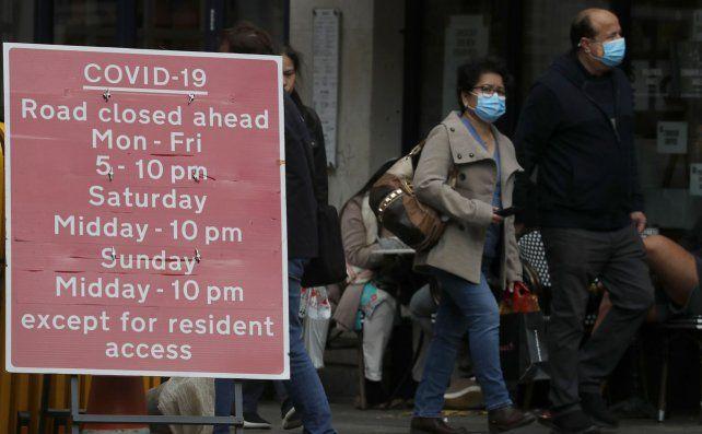 La gente pasa junto a un letrero que se refiere a los cierres de COVID-19 en Londres.