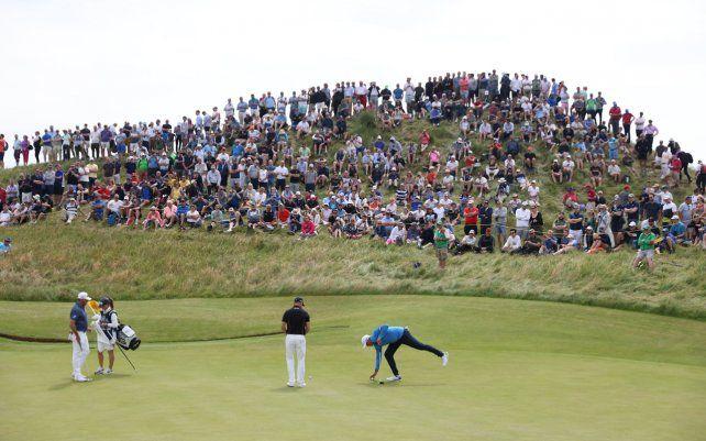 Stewart Cink de Estados Unidos recupera su pelota del hoyo en el sexto green durante la primera ronda del British Open Golf Championship en el campo de golf Royal St Georges Sandwich