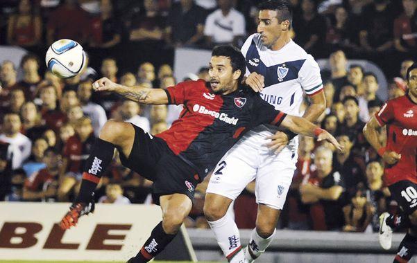 En acción. Scocco intenta pegarle a la pelota ante la marca de Pellerano. (A.Celoria)