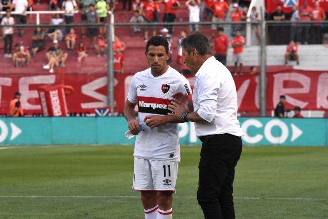 Maxi Rodríguez dialoga con el DT Frank Kudelka durante un partido