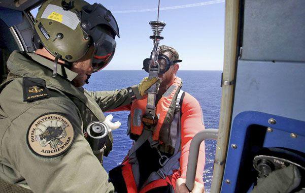 Búsqueda. El oficial de la marina australiana Daniel Colbert lanza a su compañero Joel Young al mar.