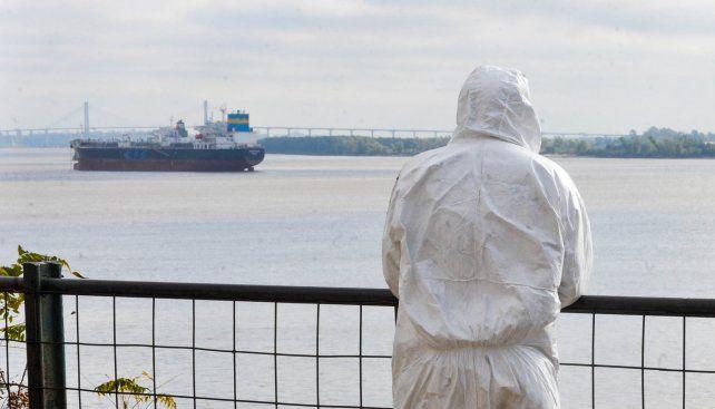 Una persona vestida con equipo de protección para el COVID contempla el río Paraná. La bajante se profundizó en los últimos días según los pronósticos del Instituto Nacional del Agua (INA).