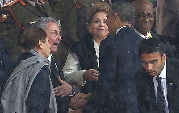 Gesto. Raúl Castro estrecha la mano de Barack Obama con quien intercambia algunas palabras frente a Dilma Rousseff.