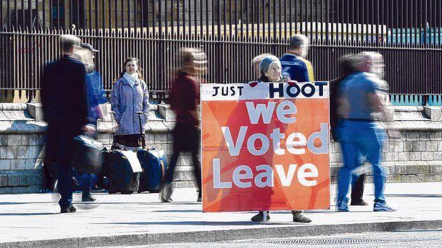 Brexit. Una partidaria de separarse de Europa sostiene una bandera que reza Sólo dime votamos por salir.