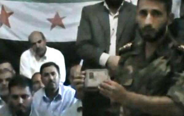 Una imagen de video muestra a un rebelde junto a los rehenes.