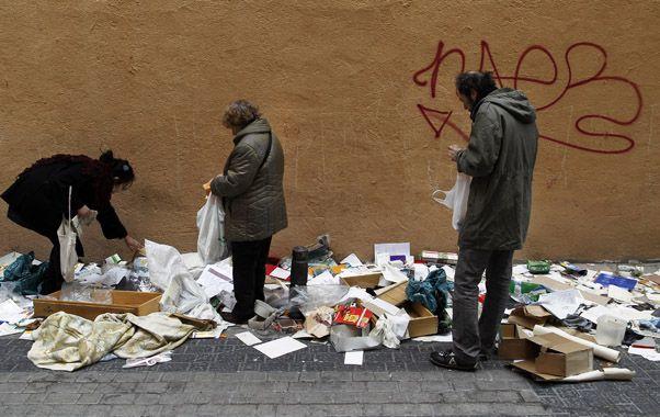 Desolador. Indigentes hurgan entre la basura dejada por una feria callejera en Madrid.