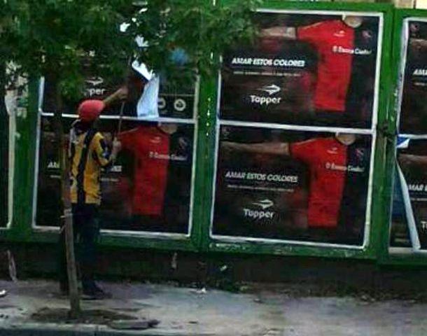 La imagen del joven con camiseta canalla pagando carteles de Newells se popularizó en las redes sociales.