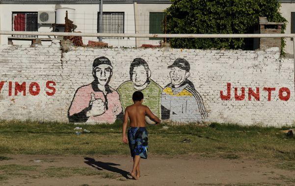 Ausencias que se sienten. Un mural recuerda a los militantes barriales asesinados en 2012 en uno de los campitos donde los pibes concurren a diario. (foto: Celina Mutti Lovera)