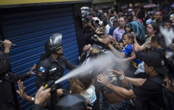 Furia popular. La policía lanza gas pimienta y bastonazos contra la multitud en el barrio carioca de Copacabana.