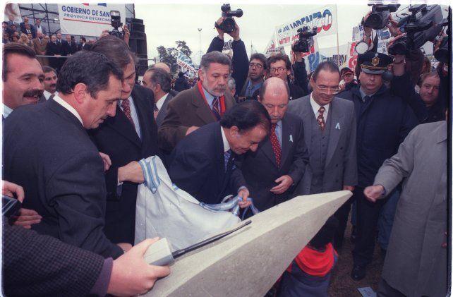 """20 de junio de 1997. El presidente Menem descubre la piedra fundamental del puente en la cabecera de Rosario.  Y promete que esta obra del puente """"será una realidad"""" y que en 1999 cuando termine su gobierno dejará a """"la Argentina entre los diez mejores países de al tierra"""". Lo primero lo cumplió, lo segundo demás está decir qué ocurrió."""