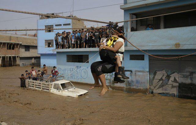 Peligro. Una mujer y su hija debieron valerse ayer de una tirolesa para cruzar una calle inundada de Lima.