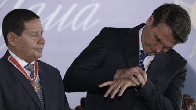 Horario. El presidente brasileño mira su reloj flanqueado por su vice